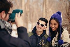 Grupo de amigos que toman las fotos inmediatas en la nieve en invierno Fotografía de archivo libre de regalías