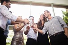 Grupo de amigos que tuestan los vidrios de champán Imagen de archivo libre de regalías