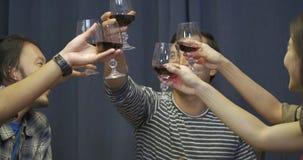 Grupo de amigos que tuestan y que beben el vino sobre partido de cena almacen de metraje de vídeo