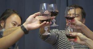 Grupo de amigos que tuestan y que beben el vino sobre partido de cena metrajes
