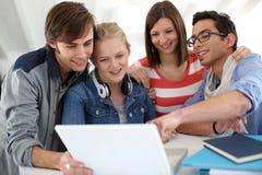 Grupo de amigos que usan el ordenador portátil en la escuela Imágenes de archivo libres de regalías