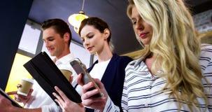 Grupo de amigos que usan el teléfono móvil y la tableta digital mientras que comiendo la taza de café almacen de video