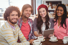 Grupo de amigos que usan la tableta digital mientras que comiendo la taza de café Fotografía de archivo