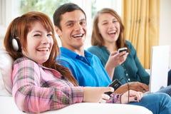 Grupo de amigos que usan la tecnología de Digitaces en casa Foto de archivo libre de regalías