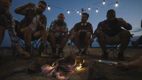 Grupo de amigos que viajan que fríen las salchichas en sitio para acampar fotos de archivo