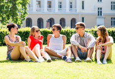 Grupo de amigos sonrientes al aire libre que se sientan en hierba Fotos de archivo libres de regalías