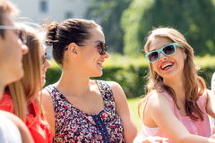 Grupo de amigos sonrientes al aire libre que se sientan en parque Foto de archivo libre de regalías
