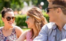 Grupo de amigos sonrientes al aire libre que se sientan en parque Imagen de archivo