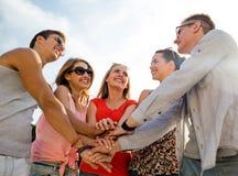 Grupo de amigos sonrientes con las manos en el top en ciudad Imágenes de archivo libres de regalías