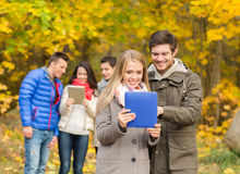 Grupo de amigos sonrientes con las tabletas en parque Foto de archivo