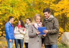 Grupo de amigos sonrientes con las tabletas en parque Imagen de archivo libre de regalías