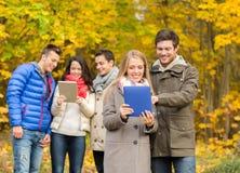 Grupo de amigos sonrientes con las tabletas en parque Fotos de archivo libres de regalías