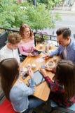 Grupo de amigos sonrientes con las tabletas y los teléfonos, relajándose en un fondo borroso Concepto de la vida del estudiante Fotografía de archivo libre de regalías