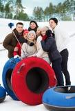 Grupo de amigos sonrientes con los tubos de la nieve Fotos de archivo