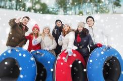 Grupo de amigos sonrientes con los tubos de la nieve Fotografía de archivo libre de regalías