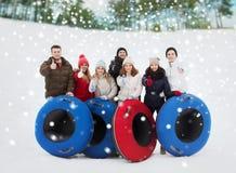 Grupo de amigos sonrientes con los tubos de la nieve fotos de archivo libres de regalías