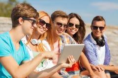 Grupo de amigos sonrientes con PC de la tableta al aire libre Imagen de archivo libre de regalías