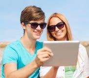 Grupo de amigos sonrientes con PC de la tableta al aire libre Imagen de archivo