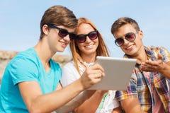Grupo de amigos sonrientes con PC de la tableta al aire libre Imagenes de archivo
