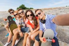 Grupo de amigos sonrientes con smartphone al aire libre Foto de archivo