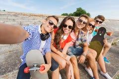 Grupo de amigos sonrientes con smartphone al aire libre Imagen de archivo