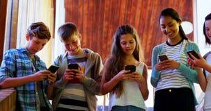 Grupo de amigos sonrientes de la escuela que usan el teléfono móvil en pasillo almacen de video