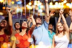 Grupo de amigos sonrientes en el concierto en club Imágenes de archivo libres de regalías