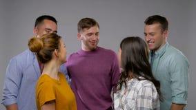 Grupo de amigos sonrientes felices sobre gris almacen de video