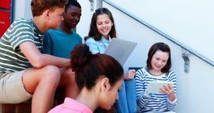 Grupo de amigos sonrientes de la escuela en escalera usando el ordenador portátil y la tableta digital metrajes