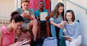 Grupo de amigos sonrientes de la escuela en escalera usando el teléfono móvil y la tableta digital metrajes