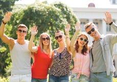 Grupo de amigos sonrientes que agitan las manos al aire libre Foto de archivo