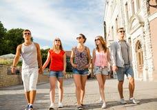 Grupo de amigos sonrientes que caminan en ciudad Fotos de archivo