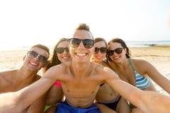 Grupo de amigos sonrientes que hacen el selfie en la playa Fotos de archivo
