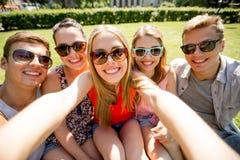 Grupo de amigos sonrientes que hacen el selfie en parque Foto de archivo