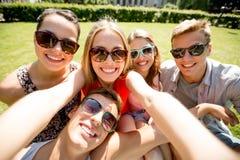 Grupo de amigos sonrientes que hacen el selfie en parque Fotografía de archivo