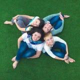 Grupo de amigos sonrientes que mienten en hierba en círculo Foto de archivo libre de regalías
