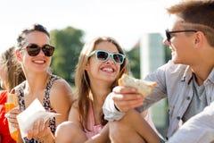 Grupo de amigos sonrientes que se sientan en cuadrado de ciudad Fotografía de archivo libre de regalías