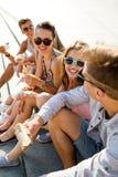 Grupo de amigos sonrientes que se sientan en cuadrado de ciudad Imagenes de archivo