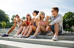 Grupo de amigos sonrientes que se sientan en cuadrado de ciudad Imagen de archivo libre de regalías