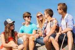 Grupo de amigos sonrientes que se sientan en la calle de la ciudad Foto de archivo