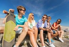 Grupo de amigos sonrientes que se sientan en la calle de la ciudad Fotografía de archivo libre de regalías