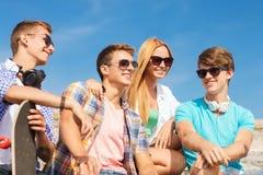 Grupo de amigos sonrientes que se sientan en la calle de la ciudad Imagen de archivo