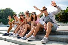 Grupo de amigos sonrientes que se sientan en la calle de la ciudad Fotos de archivo libres de regalías
