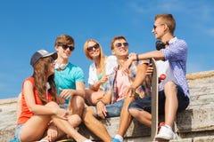 Grupo de amigos sonrientes que se sientan en la calle de la ciudad Imagenes de archivo