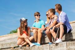 Grupo de amigos sonrientes que se sientan en la calle de la ciudad Foto de archivo libre de regalías