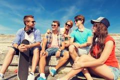 Grupo de amigos sonrientes que se sientan en la calle de la ciudad Fotos de archivo
