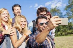 Grupo de amigos sonrientes que toman el selfie Imagen de archivo