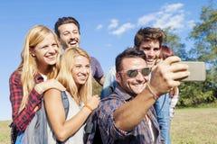 Grupo de amigos sonrientes que toman el selfie Imagen de archivo libre de regalías
