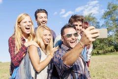 Grupo de amigos sonrientes que toman el selfie Imagenes de archivo