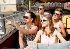 Grupo de amigos sonrientes que viajan en bus turístico Imágenes de archivo libres de regalías